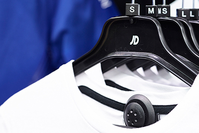 CU of the Agon Systems Concept Tag EAS tagging system on a white t-shirt in JD Sports