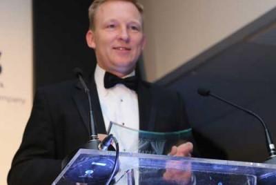 Sean Welch at a pedestal accepting a Retail Fraud Award in 2106